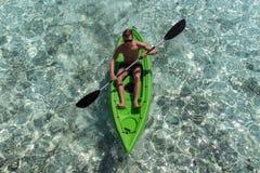 Giovane kayak felice dell'uomo su un'isola tropicale in Maldive Acqua blu libera immagini stock libere da diritti