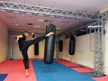 Giovane kickboxer che dà dei calci al punching ball nella palestra di sport Immagine Stock