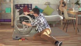 Giovane latino-americano riparazioni di un disabile la sua sedia a rotelle video d archivio