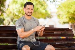 Giovane latino che ascolta la musica in un parco immagini stock