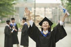 Giovane laureato femminile dell'università, armi alzate nell'aria con il diploma Fotografie Stock Libere da Diritti