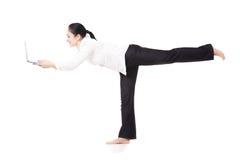 Giovane lavoratore corporativo in computer portatile della tenuta di posa di yoga sulla parte posteriore di bianco Fotografie Stock Libere da Diritti