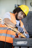 Giovane lavoratore manuale in metallo protettivo della macinazione degli abiti da lavoro nell'industria fotografia stock
