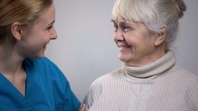 Giovane lavoratore medico che parla con signora anziana sorridente in ospedale, buone notizie fotografia stock