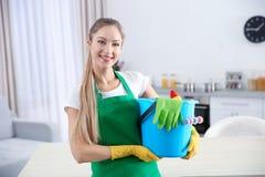 Giovane lavoratrice con i rifornimenti di pulizia immagini stock