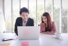 Giovane lavoro asiatico dell'uomo di affari con il computer portatile nell'ufficio fotografia stock libera da diritti