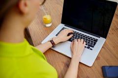 Giovane lavoro della donna di affari sul testo di battitura a macchina del netbook durante la prima colazione in caffetteria mode Fotografie Stock