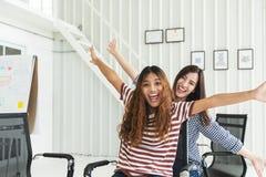 Giovane lavoro di squadra creativo multietnico due divertendosi risata, sorridere e seduta nelle sedie dell'ufficio Donne del col Immagine Stock Libera da Diritti