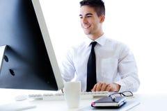 Giovane lavoro felice dell'uomo di affari in ufficio moderno sul computer Fotografia Stock Libera da Diritti