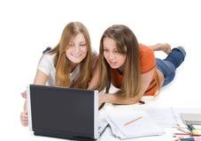 Giovane lavoro felice della ragazza dell'allievo due sul computer portatile Fotografia Stock Libera da Diritti