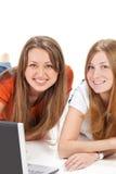 Giovane lavoro felice della ragazza dell'allievo due sul computer portatile Immagine Stock