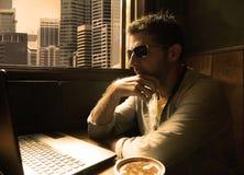 Giovane giovane lavoro felice e riuscito attraente dell'uomo d'affari rilassato dalla caffetteria di Internet con il computer por immagine stock libera da diritti