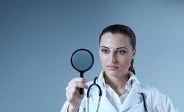 Giovane lente d'ingrandimento femminile della holding del medico in ri Fotografia Stock