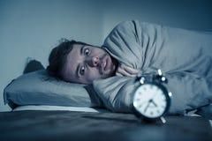 Giovane a letto con la sensibilit? della sveglia disperata e l'emergenza non capace di dormire con insonnia fotografia stock libera da diritti