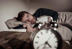 Giovane a letto con la sensibilit? della sveglia disperata e l'emergenza non capace di dormire con insonnia fotografie stock libere da diritti