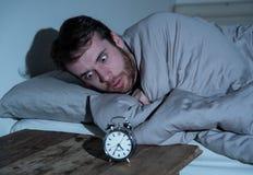Giovane a letto con la sensibilit? della sveglia disperata e l'emergenza non capace di dormire con insonnia immagine stock