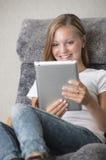 Giovane lettura della femmina adulta su un pc del ridurre in pani fotografie stock