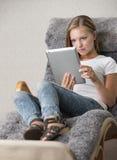 Giovane lettura della femmina adulta su un pc del ridurre in pani Immagine Stock