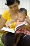 Giovane lettura della madre mentre babysitting fotografie stock libere da diritti