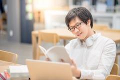Giovane libro di lettura asiatico dello studente universitario dell'uomo in biblioteca Fotografia Stock Libera da Diritti