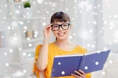 Giovane libro di lettura asiatico sorridente della donna a casa Immagini Stock