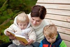 Giovane libro di lettura del bambino e della madre esterno immagine stock libera da diritti