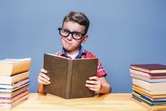 Giovane libro di lettura dell'allievo nella biblioteca di scuola Immagini Stock