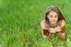Giovane libro di lettura dell'donna-allievo sopra Fotografie Stock Libere da Diritti