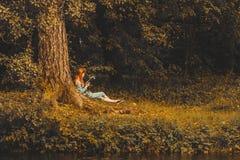 Giovane libro di lettura della donna della testarossa nel parco di autunno Fotografia Stock