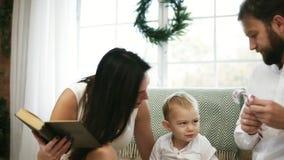Giovane libro di lettura della madre per il suoi figlio e marito Storia di Natale della lettura della famiglia mentre sedendosi d video d archivio