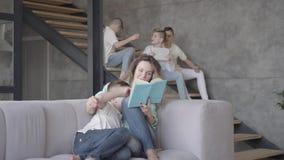 Giovane libro di lettura grazioso della madre a suo figlio mentre il resto dei suoi bambini teenager che giocano a vicenda nei pr stock footage