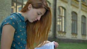 Giovane libro di lettura pensieroso serio della donna dello zenzero ed esaminare macchina fotografica, sedentesi sulla via con co video d archivio