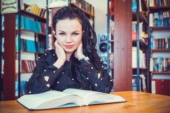 Giovane libro di modello sveglio della tenuta della ragazza alla biblioteca Immagini Stock Libere da Diritti