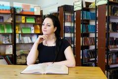 Giovane libro di modello sveglio della tenuta della ragazza alla biblioteca Immagine Stock Libera da Diritti