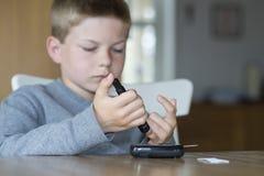 Giovane livello del glucosio di misura del ragazzo fotografie stock