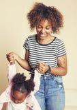 Giovane madre afroamericana dolce adorabile con la piccola figlia sveglia, appendendo a casa, divertendosi giocando sorridere Immagine Stock