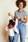 Giovane madre afroamericana dolce adorabile con la piccola figlia sveglia, appendendo a casa, divertendosi giocando sorridere Fotografia Stock Libera da Diritti