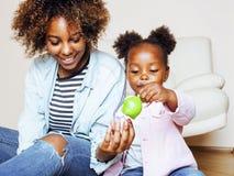 Giovane madre afroamericana dolce adorabile con la piccola figlia sveglia, appendendo a casa, divertendosi giocando sorridere Fotografie Stock