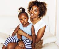 Giovane madre afroamericana dolce adorabile con la piccola figlia sveglia, appendendo a casa, divertendosi giocando sorridere Immagini Stock