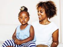 Giovane madre afroamericana dolce adorabile con la piccola figlia sveglia, appendendo a casa, divertendosi giocando sorridere Immagine Stock Libera da Diritti