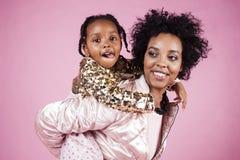 Giovane madre afroamericana graziosa con la piccola figlia sveglia che abbraccia, sorridere felice sul fondo rosa, stile di vita Immagine Stock Libera da Diritti