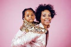Giovane madre afroamericana graziosa con la piccola figlia sveglia che abbraccia, sorridere felice sul fondo rosa, stile di vita Fotografia Stock