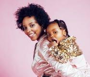 Giovane madre afroamericana graziosa con la piccola figlia sveglia che abbraccia, sorridere felice sul fondo rosa, stile di vita Immagini Stock Libere da Diritti