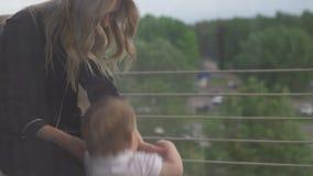Giovane madre bionda con il neonato triste che guarda attraverso la finestra che pensa allo scopo di budoir nero d'uso vita stock footage