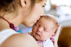Giovane madre a casa che tiene sua figlia del neonato immagini stock libere da diritti