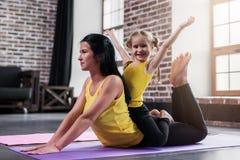 Giovane madre caucasica che fa posa della cobra di yoga sul pavimento mentre sua figlia sorridente che si siede sulle mamme indie immagini stock
