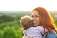 Giovane madre che abbraccia bambino, sorridente sulla bella vista panoramica dietro fotografie stock