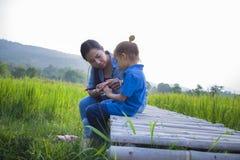 Giovane madre che abbraccia e che lenisce un piccolo ragazzo lungo gridante dei capelli, una madre asiatica provanti a confortare immagini stock