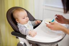 Giovane madre che alimenta il suo piccolo figlio del bambino con porridge, che sedendosi nell'alta sedia del bambino per alimenta Immagini Stock Libere da Diritti