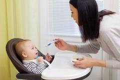 Giovane madre che alimenta il suo piccolo figlio del bambino con porridge, che sedendosi nell'alta sedia del bambino per alimenta Immagine Stock
